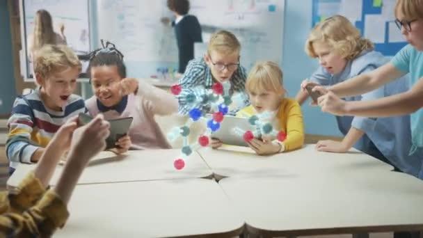 Schulkinder im Chemieunterricht verwenden digitale Tablet-Computer mit Augmented-Reality-Anwendung und betrachten die 3D-Animation eines Moleküls. VFX, Special Effects Render