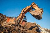 Photo Big orange excavator in the coal mine