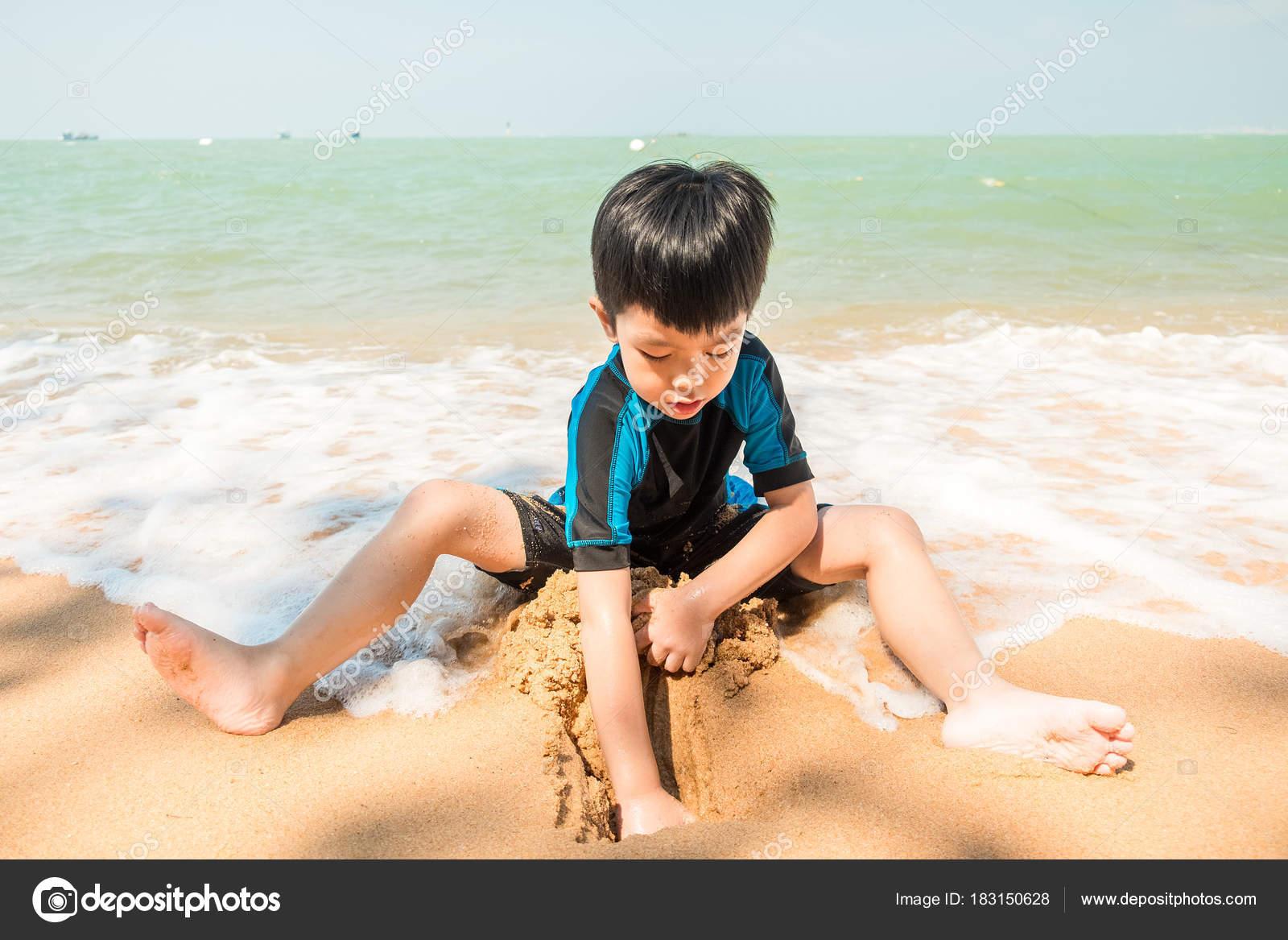 Costume Da Bagno Ragazzo : Un ragazzo in costume da bagno è seduta sulla spiaggia e giocando