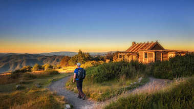 Young hiker with backpack approaching a hut in Australia