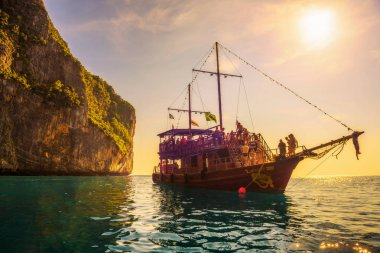 Boat in pirate style with many tourists at Maya Bay in Thailand