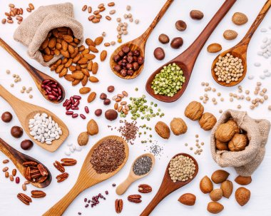 Various legumes and different kinds of nuts in spoons. Walnuts k