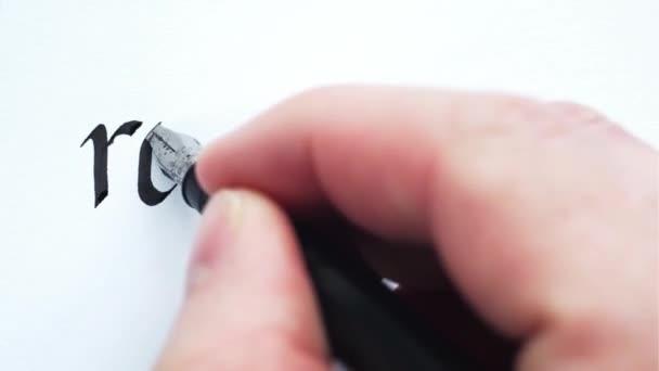 Schreiben des Wortes Vergeltung. Männliche Hände schreiben mit einem Stift. Kalligraphie Nahaufnahme.