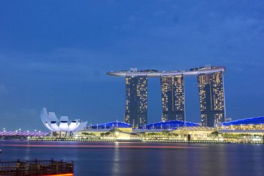 Marina Bay Sands hotel and Art and Science Museum at summer night with the blue sky