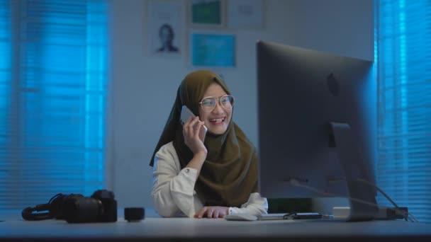 schöne muslimische Asiaten, waren in einem Anruf, wenn sie nachts von zu Hause aus in einem modernen Interior Design Coworking Space arbeiteten