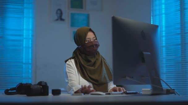 krásný muslimský Asiat, byli ve volání při práci z domova v noci v moderním interiérovém designu coworking prostor