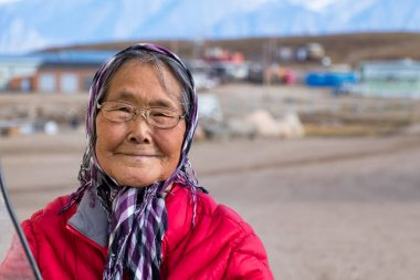 Pond Inlet, Baffin Island, Canada - August 23, 2019: Portrait of a eskimo - inuit senior woman outdoors in Pond Inlet, Baffin Island, Canada.