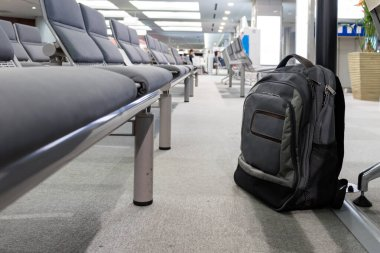 Unattended cabin backpack abandoned on the floor at airport.