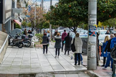 People waiting to enter to a supermarket outside keeping safe distance. Athens, Greece.