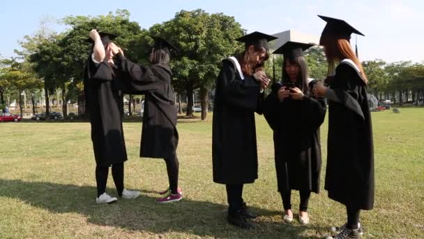 Portrait of excited asia group of friends on graduation day. They are outdoors on campus in a natural green landscape with university building in the background.-Dan