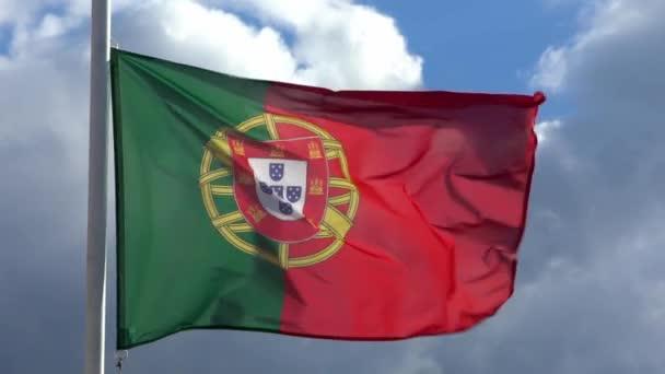 A portugál zászló lassú mozgása lengett a szélben egy város zászlórúdján. A portugál zászlók lassított mozgása lebeg nappal a kék ég előtt. Közelről egy igazi szövet textúra zászlós csapkodó - Dan