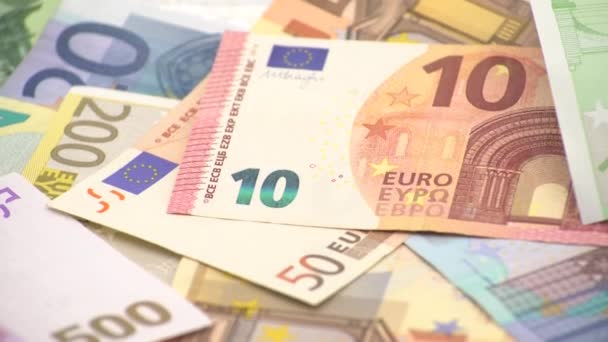 4K Closeup of a coin one euro with banknotes of different values. Cash money background. Real hundred euros. Good earnings. Issuing salary. Credit percent. Successful business. Dolly sliding shot-Dan