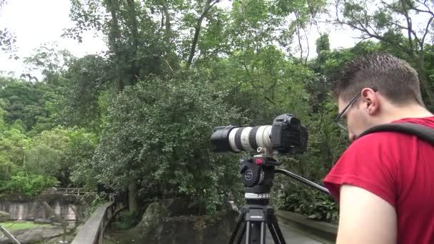 Kaukázusi fotós képeket készít DSLR kamerával. Turista utazási fotós fényképezés a természet a parkban-Dan