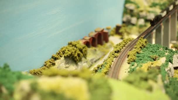 Miniatur-Modelleisenbahn Dampfzug mit Waggons fährt, verschwommene Bewegung-Dan