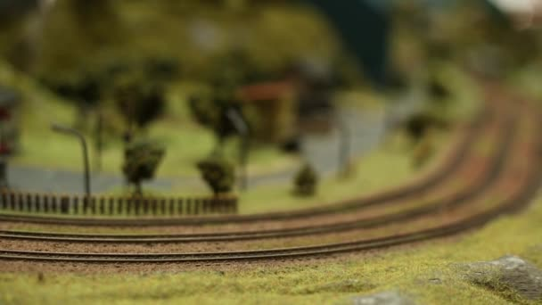 Miniatur-Modelleisenbahn, Zug mit Waggons fährt, verschwommene Bewegung-Dan