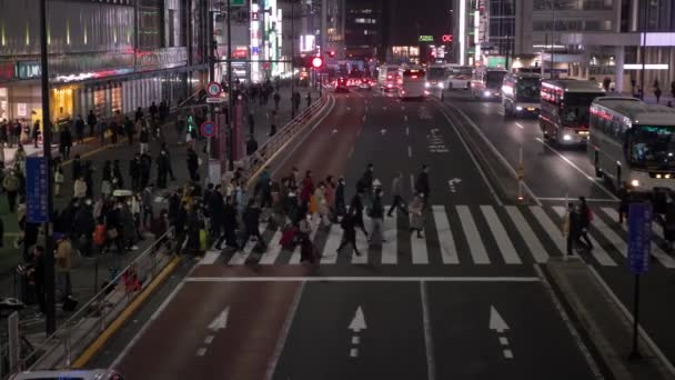 Tokyo, Japan-31 January, 2020: 4K Aerial of crowd people locals and tourists walking in busy neighbourhood street near metro station. Railway station area with pedestrian walking around on evening-Dan