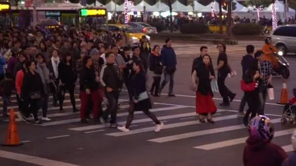Taipei, Taiwan-05 February, 2017: Sidewalk view of walking crowd people crossing street in Taipei City. Pedestrians walk across road on busy city streets. Crowds of asian crossroad in crowded -Dan