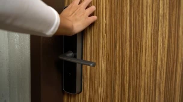 4K, Frau drückt digitale Nummern, um die Holztür zu öffnen und ins Haus zu gehen. Blaue Zahlen im elektronischen Türschutz entriegeln. Mädchen öffnet die intelligente Sicherheitstür des Zimmers. Technologie im eigenen Land