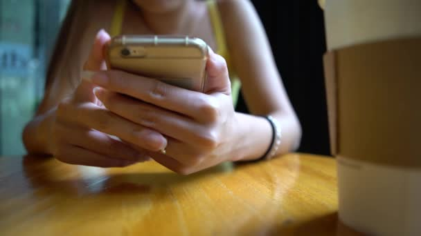 4K Asian Woman Using Smartphone in a coffeeshop. Dobrý čas na odpočinek a vychutnat si kávu. Surfování na internetu, kontroluje sociální sítě chat a kontaktovat lidi se svým telefonním zařízením-Dan