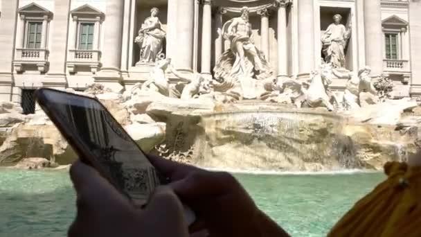 4K, Close up of female hand hold and touch screen smartphone with Trevi Fountain at background. Asijka používající mobil. Dívka posílá zprávy po telefonu. Lidé cestující pomocí zařízení mobile-Dan