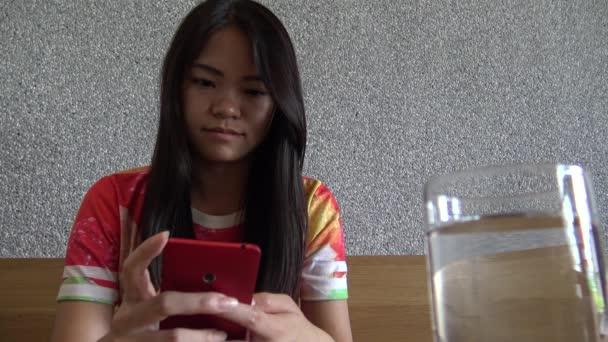 4K Hd Ultra, asijská mladá žena pitná voda a užívat smartphone v kavárně, dobrý čas vidět sociální síť s telefonem zařízení, pomocí mobilních e-mailů, obrázky, psát text. Tchaj-wan.