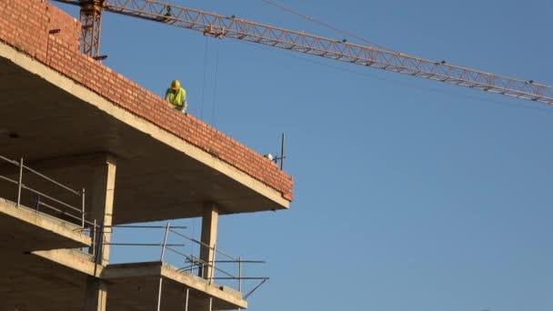 Sevilla, Španělsko-03 Leden, 2019: 4k, Zedníkový betonářský zdivo stavět vrstvu domu dělník. Nový dům ve výstavbě za slunečného dne. Pouto z hliněných cihel za použití cementové malty.