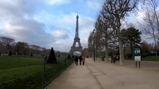 Paris, France-13 January, 2018: 4K, Champ de Mars and the Eiffel Tower in winter day. Green trees and cloudy sky, people walking around. Famous touristic places and popular travel destinations-Dan