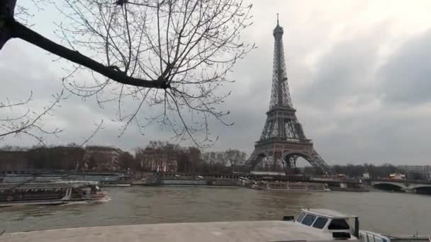 4K, Eiffel Tower and Seine river with boat in back of tree branches of a winter day Paris, France. Trees and cloudy sky in famous touristic places Europe. Rainy day with the tour Eiffel background-Dan