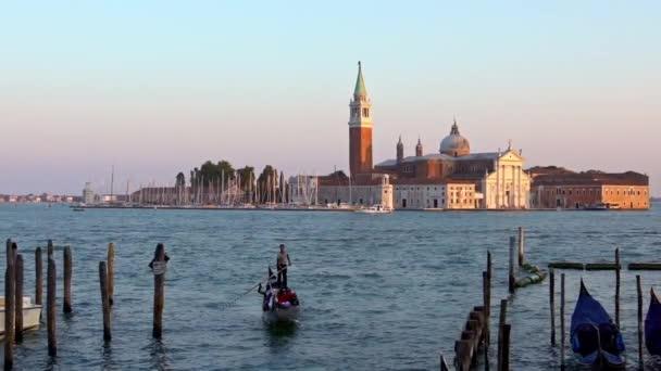 Benátky, Itálie-21. září 2018: Pomalý pohyb tradiční benátské gondoliérky punting gondoly s historickým kostelem San Giorgio Maggiore v pozadí Benátek Itálie. Romantické cestování - Dan