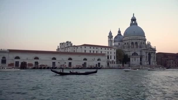 Velence, Olaszország-21 szeptember, 2018: 4K, Beautiful view of Basilica Santa Maria della Salute and traditional gondola in Grand Canal. Gondolák egy szállítás körül a velencei csatornák - Dan