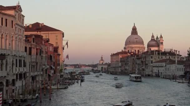 Benátky, Itálie-20 Září, 2018: 4K, Krásný výhled Bazilika Santa Maria della Salute s lodí a trajekty křižující po vodní cestě v Grand Canal. Trajekt je přeprava po benátských kanálech-Dan