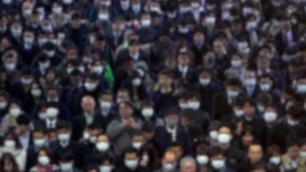 Zeitlupe Unscharfe, defokussierte Ansicht der Luftaufnahme große Menschenmenge, die eine chirurgische Maske trägt und in den Ausgang der U-Bahn geht. Coronavirus-Lungenentzündung breitet sich in Städten aus. 2019-nCoV-Epidemie in China-Dan