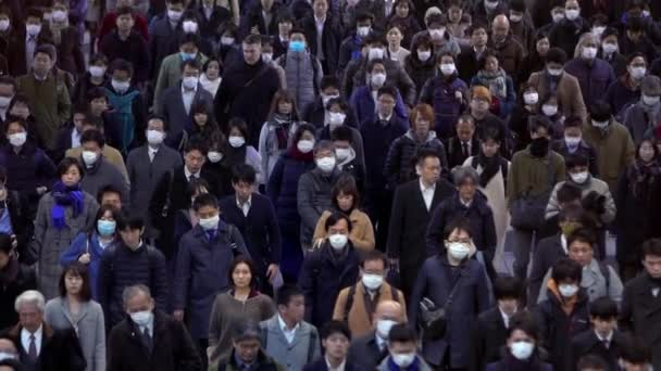 Tokyo, Japan-04 February, 2020: Slow motion high angle view, people locals and tourists wearing protective mask against transmissible infectious diseases and protection the flu in public transport-Dan