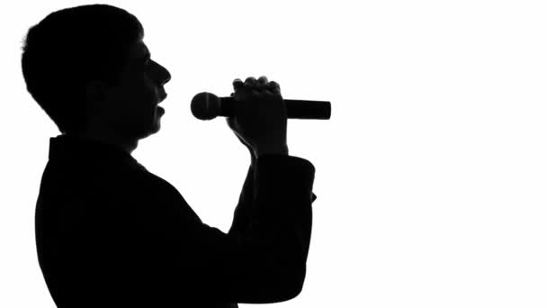 Photo silhouette video of a man singing a song with a microphone