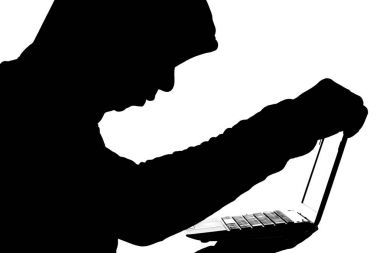 fraudster opening a laptop to gain access to information and finance