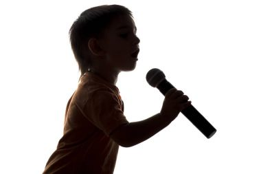 Silhouette of little happy boy singing into microphone