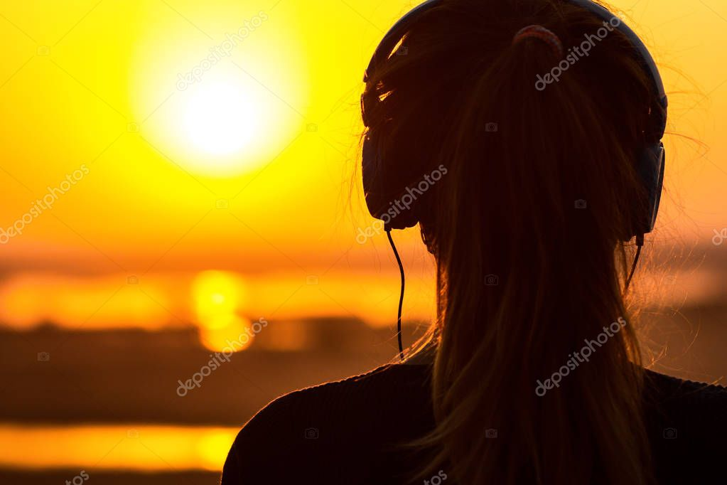 silhouette of a woman in headphones, the girl enjoying music on the sunset