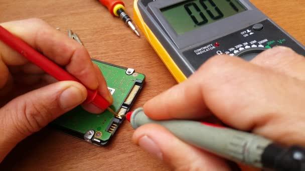 mistr rádiového inženýrství opravuje část počítače, pomocí digitálního multimetru na něm provádí měření, ruce mistra jsou viditelné