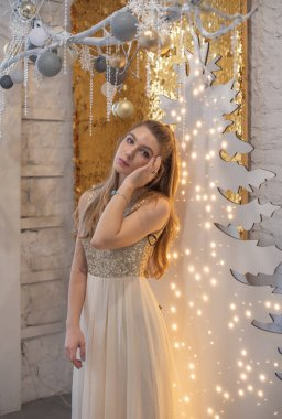 girl in a shiny evening dress. Christmas Eve. Cozy holiday at the fur-tree with lights and gold decor