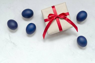 modern trendy classically blue Easter eggs of the original color and a gift with a red ribbon on a light background close-up with a place for text. flatlay. blank for text, advertising, lettering