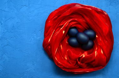 blue trendy modern eggs in a red silk nest on a classic blue background with place for text