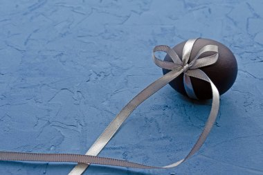blue egg with a gray satin ribbon on a classic blue background with place for text