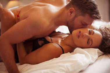 Intimate copule kissing in the bed.