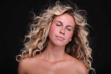 Beauty portrait of the blonde woman with curly hair on the black background.