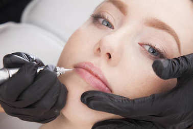 Close up on beautician doing a permanent make up of lips.