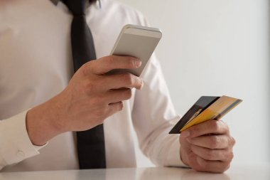 The hands of business people holding credit cards and smartphones for online shopping and paying via the internet.
