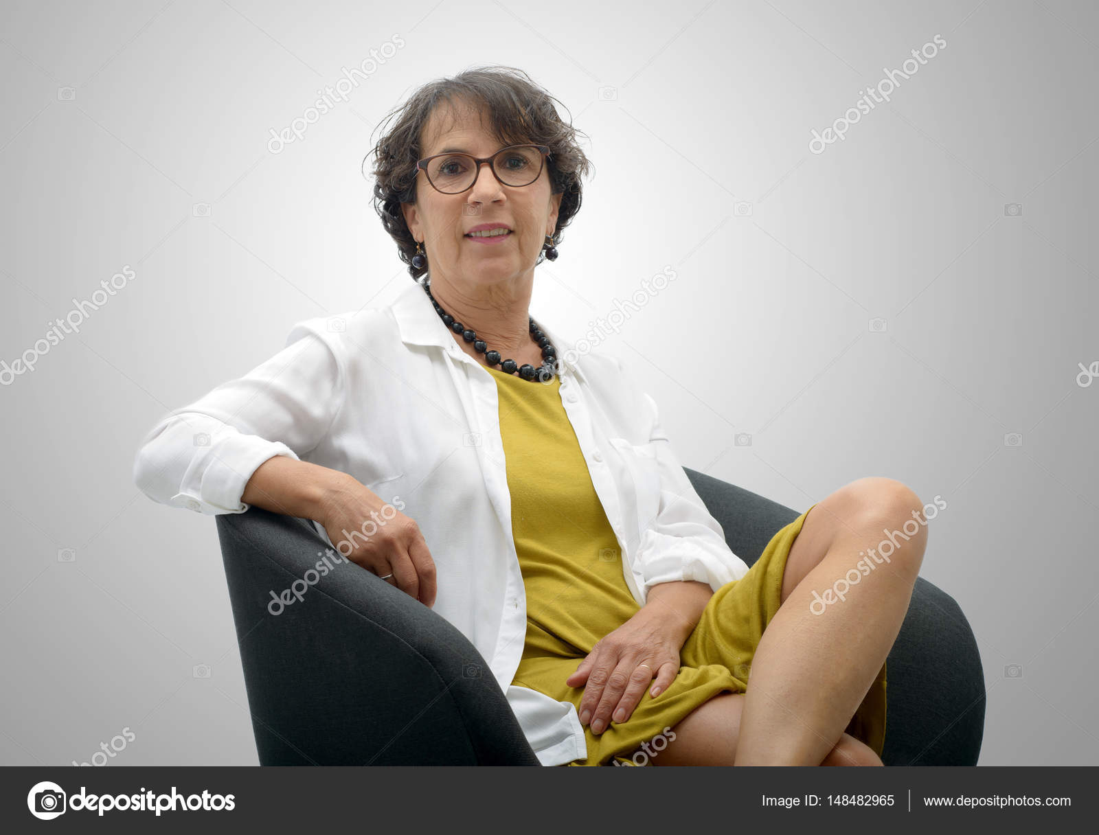 attractive mature woman sitting on a black chair — stock photo