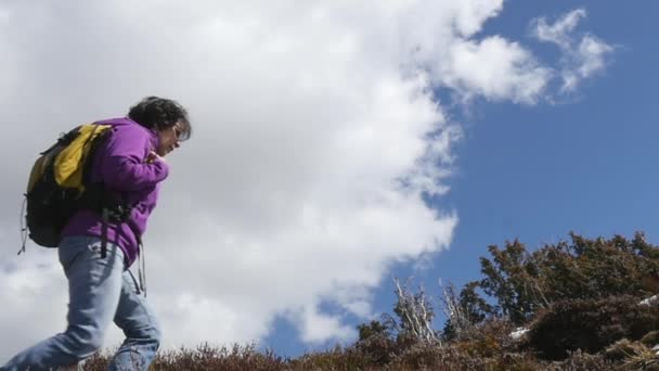 woman hiker with backpack walking a trail in mountains in slow motion
