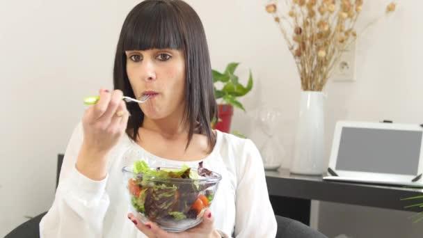 hübsche junge brünette Frau isst Salat