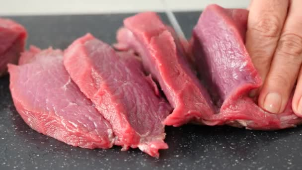 rohes Rindfleisch in Nahaufnahme auf einem Schneidebrett schneiden